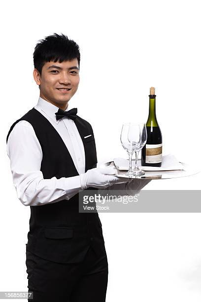 Waiter carrying wine bottle and glasses