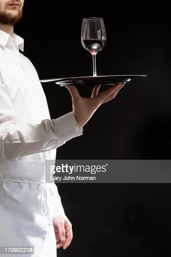 waiter carrying wine glass on server