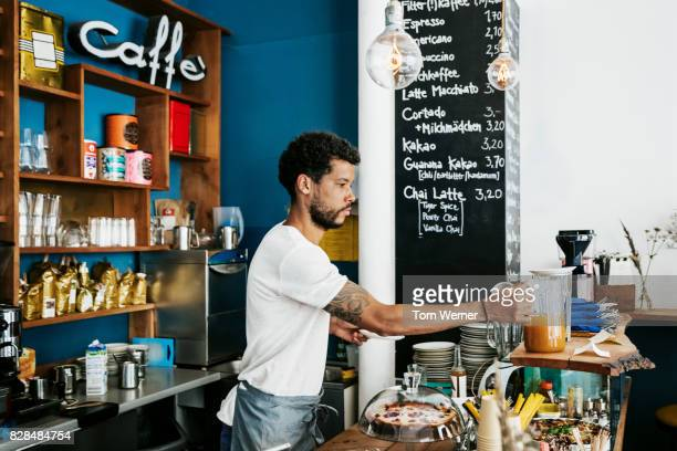 Waiter Cleaning And Organising Cafe Counter