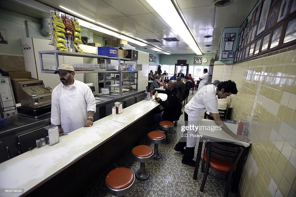 A waiter clears a table at Lafayette Coney Island restaurant February 24, 2013 in Detroit, Michigan. The city of Detroit has faced serious economic challenges in the past decade, with a shrinking population and tax base while trying to maintain essential services. A financial review team issued a finding on February 19 identifying the city as being under a 'financial emergency.' Michigan Gov. Rick Snyder has 30 days from the report's issuance to officially declare a financial emergency, which could result in the governor appointing an emergency financial manager to oversee Detroit's municipal government.