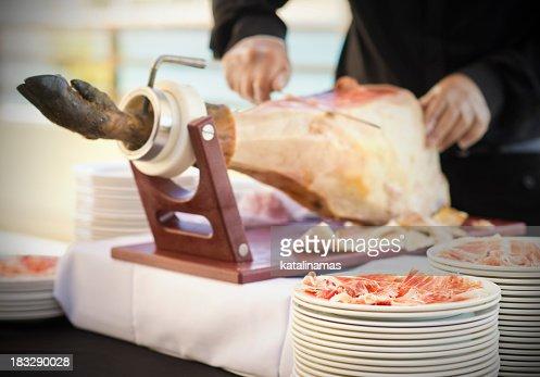 Waiter cutting slices of Spanish Serrano ham