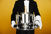 Waiter delivering champagne on silver platter