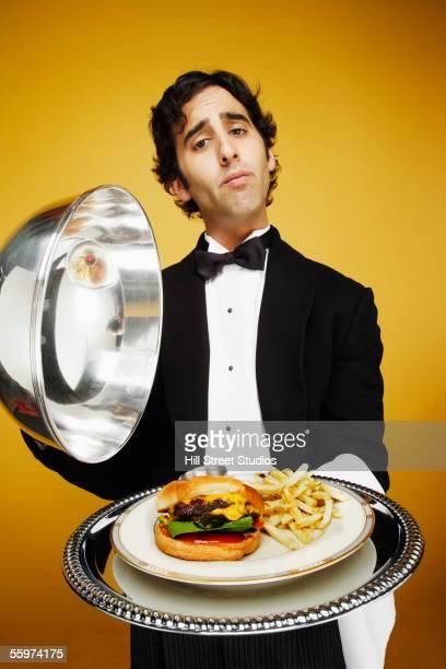 Waiter delivering hamburger on silver platter