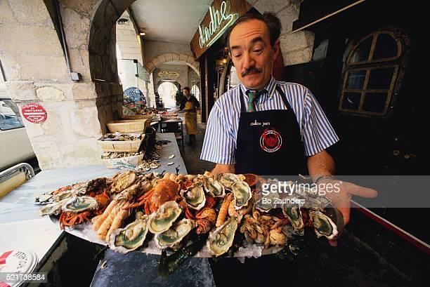 Waiter Delivering Large Seafood Dish