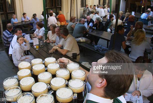 A waiter distributes glasses of dark beer to tourists June 21 at the famed U Fleku pub in Prague Czech Republic Pub life and beer are an intrinsic...