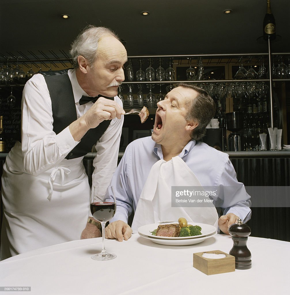 Waiter feeding man portion of meat on fork in restaurant : Stock Photo