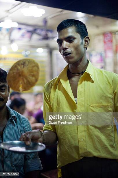 A waiter flips a cooked paratha on a plate at Parawthe Wala restaurant in Old Delhi India The parantha is an Indian fried bread folded and filled...