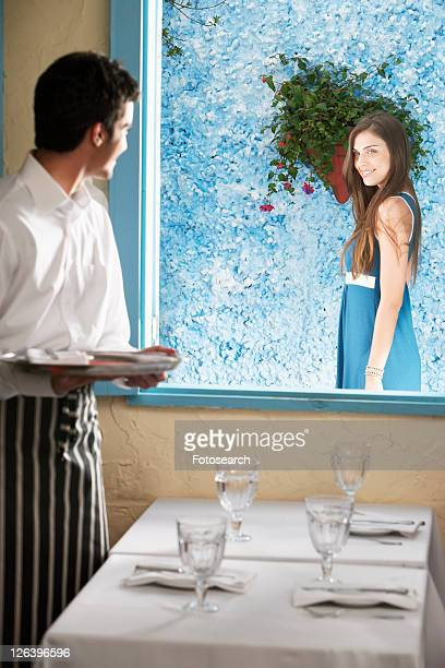 Waiter flirting with woman at window