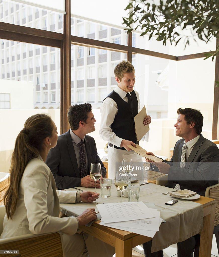 Waiter handing business people menus at restaurant table : Stock Photo