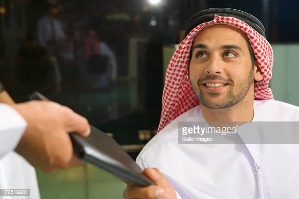 Waiter Hands the Bill to Arab Man in Restaurant. Dubai, United Arab Emirates
