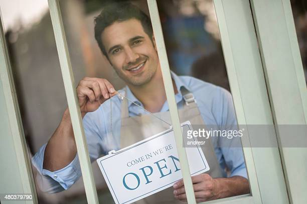 Waiter hanging an open sign at a restaurant