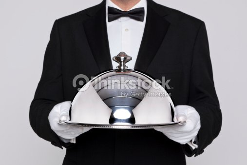 Waiter holding a silver cloche : Stock Photo