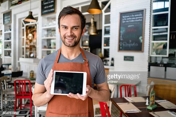 Waiter holding a tablet computer at the restaurant
