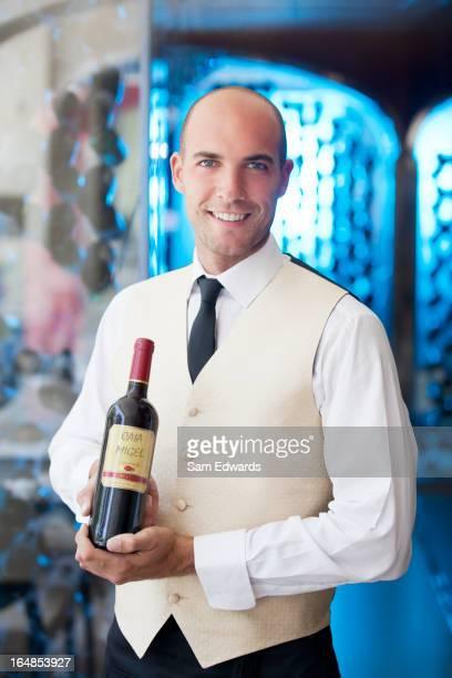 Waiter holding bottle of wine in restaurant