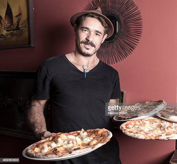 Waiter holding fresh cooked pizza