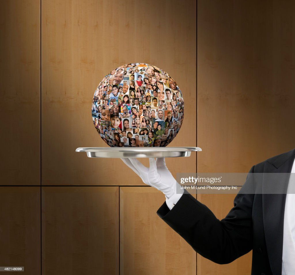 Waiter holding globe collage of business people's faces : Foto stock