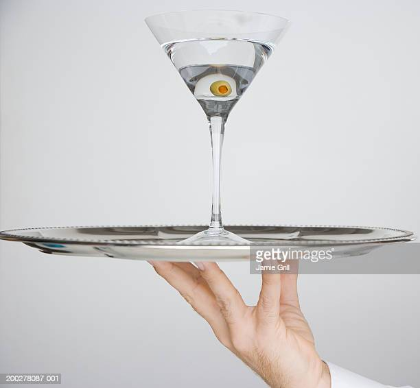 Waiter holding martini on tray, close-up