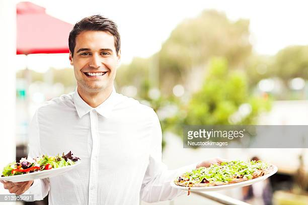Waiter Holding Salad And Pizza In Restaurant