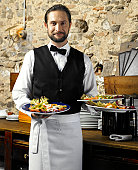 Waiter holding three plates of salad, smiling, portrait