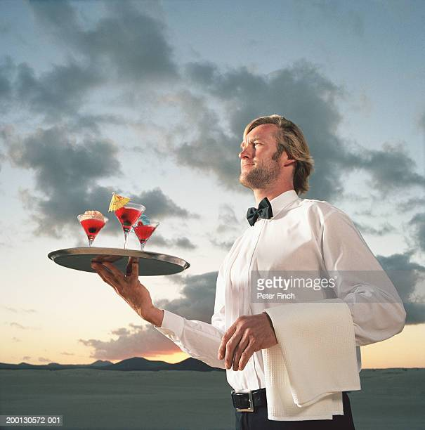 Waiter holding tray of cocktails by desert