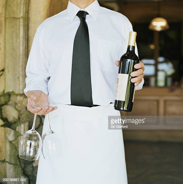 Waiter holding wine and glasses (mid section)