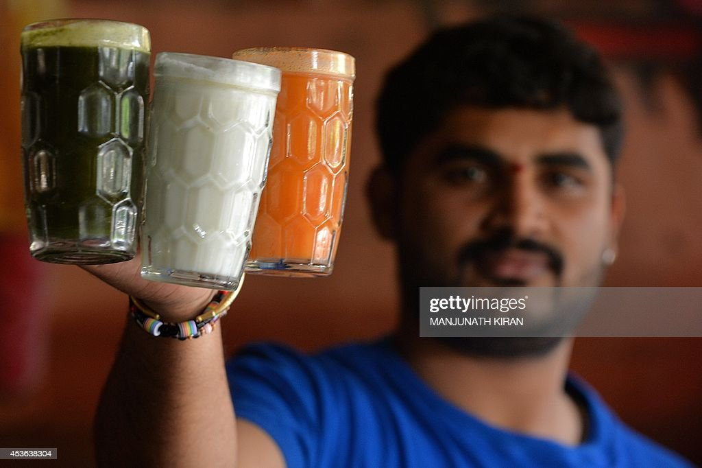 A waiter in a hotel displays specially prepared drinks prepared in the Indian tri-colours at a hotel in Bangalore on August 15, 2014. The hotel management has taken a unique approach to attract customers and also to celebrate the 68th Independence Day by preparing several food dishes in orange, white and green colours which represent the Indian flag. AFP PHOTO/Manjunath KIRAN