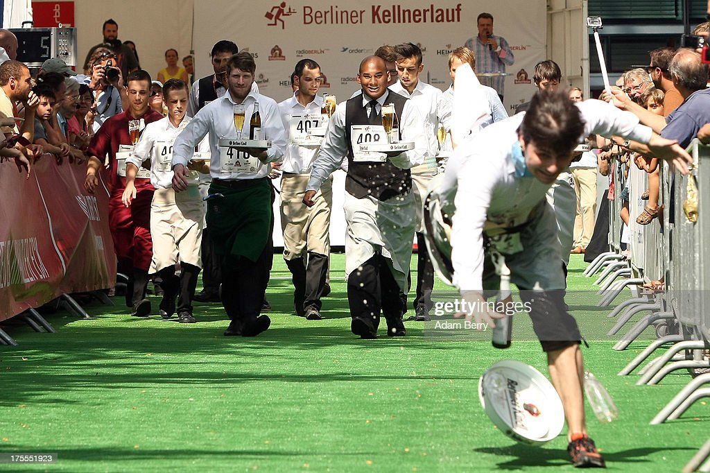 A waiter in the lead trips and falls during the Waiters' Derby (Kellner Derby in German) on August 4, 2013 in Berlin, Germany. At the annual event, brought back into existence in 2011 on the 125th anniversary of the Kurfuerstendamm (known locally as the Ku'damm), a main shopping thoroughfare, waiters, porters, cooks and bartenders run a 400-meter track while performing their regular occupational duties. The event was reinstated after a hiatus since the 1950s, when it was created to bring a sense of normal life back to Berlin after World War II under the Allies, a period in which gastronomical interest in the isolated Western part of the city suffered.