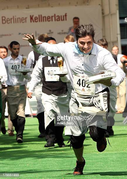 A waiter in the lead trips and falls during the Waiters' Derby on August 4 2013 in Berlin Germany At the annual event brought back into existence in...