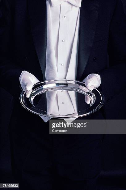 Waiter in tuxedo holding silver tray