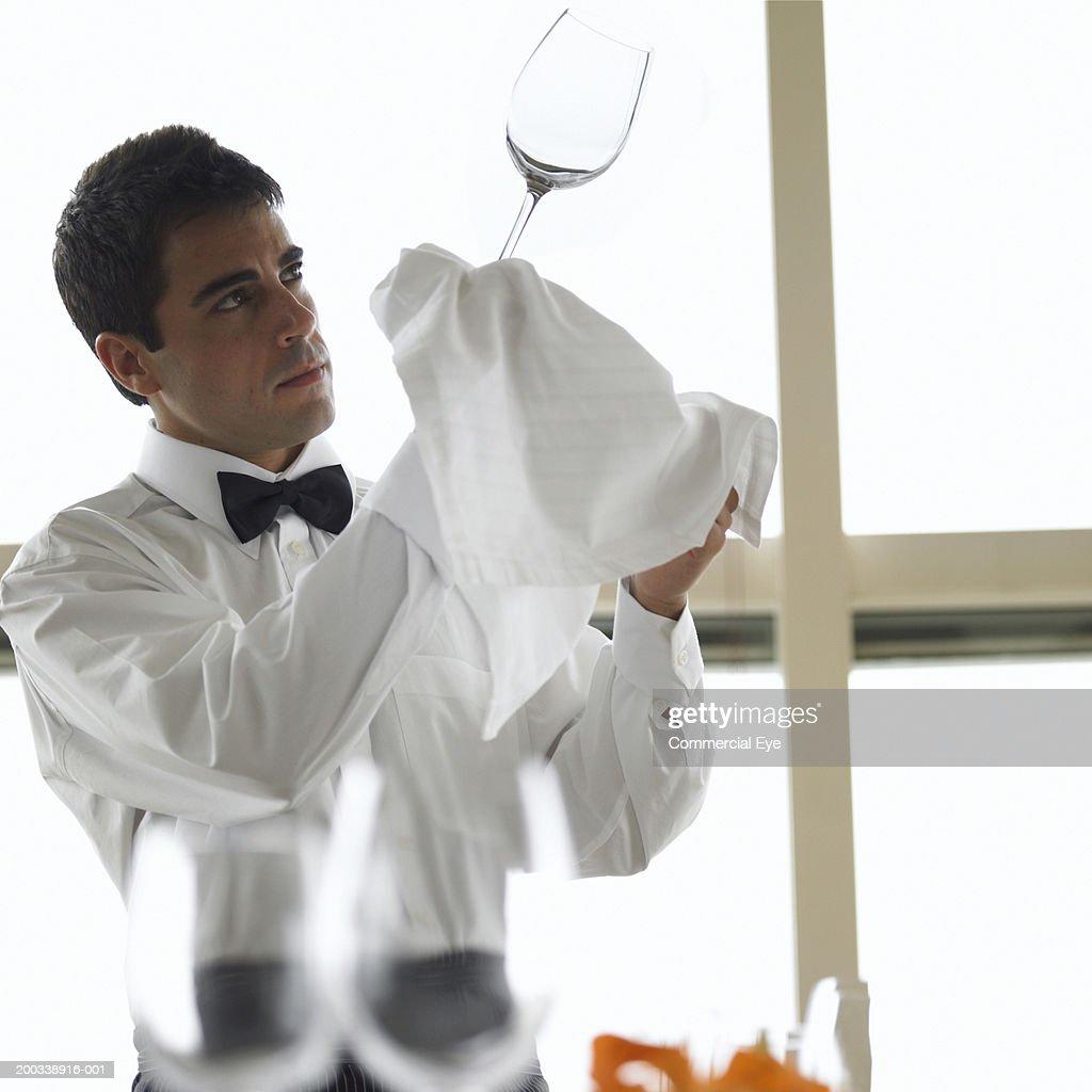 Waiter inspecting wine glass against light, side view : Stock Photo