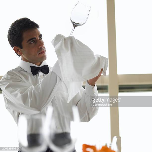 Waiter inspecting wine glass against light, side view