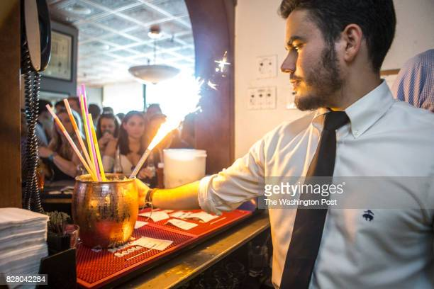 Waiter Juan Zaita prepares to deliver the Mega Mule a 120oz Moscow Mule ordered by an intern at The Front Page