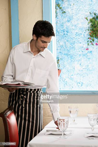 Waiter laying table