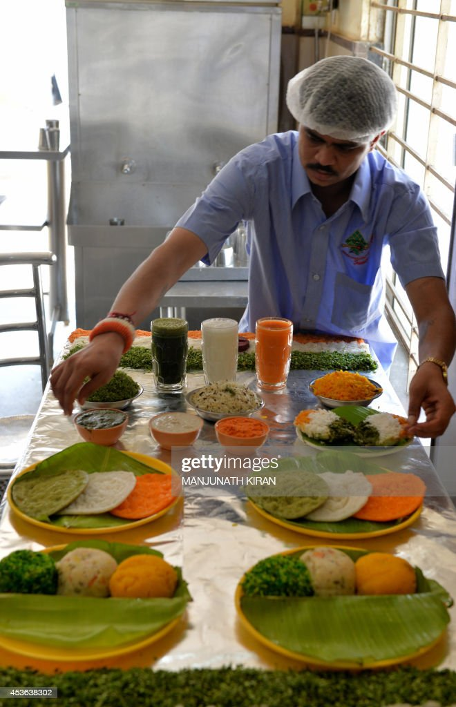 A waiter lays out food items prepared in the Indian tri-colours at a hotel in Bangalore on August 15, 2014. The hotel management has taken a unique approach to attract customers and also to celebrate the 68th Independence Day by preparing several food dishes in orange, white and green colours which represent the Indian flag. AFP PHOTO/Manjunath KIRAN