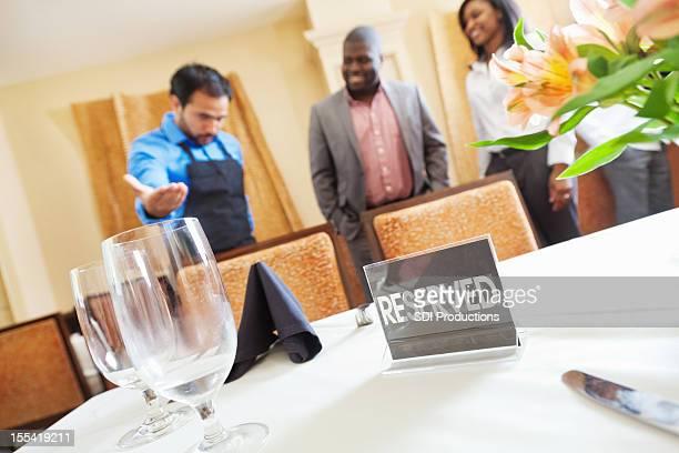 ウェイターをするカップル、ご予約には、レストランのテーブル