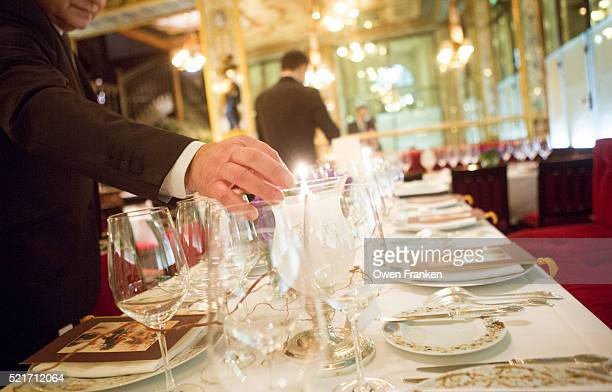 Waiter lighting candles before dinner service at the restaurant Le Grand Vefour, Paris