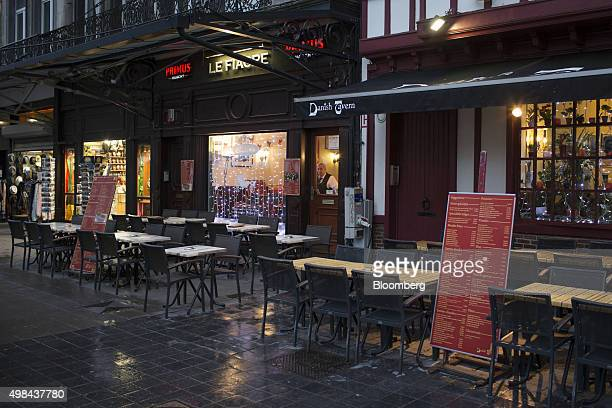 A waiter looks out onto empty restaurant tables and seating near Grand Place square in Brussels Belgium on Sunday Nov 22 2015 The search for a key...