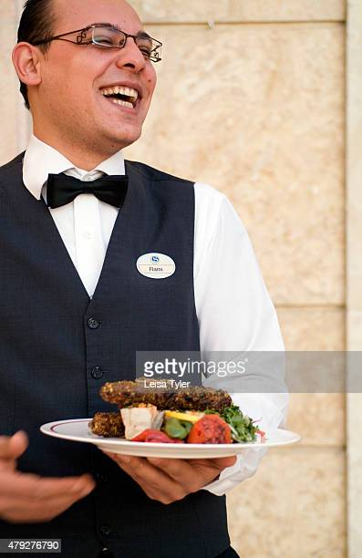 A waiter of the Sheraton in Aleppo Syria holding a plate with Kabbab Azmerly Famous throughout the Middle East for its techniques and zesty flavours...
