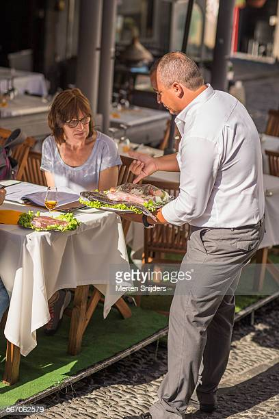 Waiter offering catch of the day choice