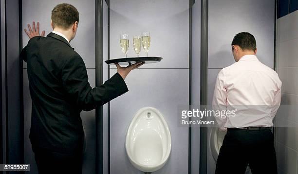 A waiter offers glasses of Champagne to VIP guests in a newly refurbished public toilet in Oxford Street on May 20 2005 in London Westminster City...