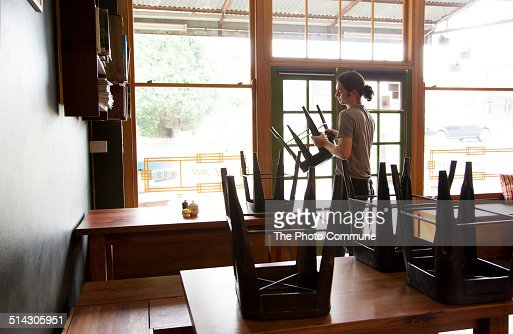 Waiter packing up cafe or restaurant chairs