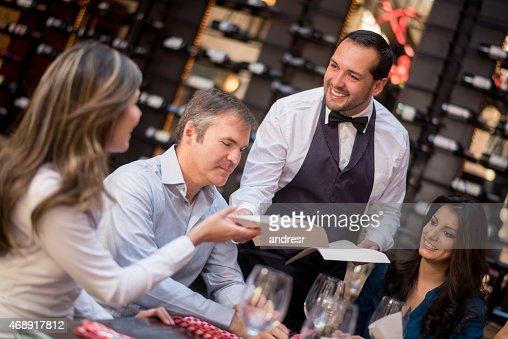 Waiter passing menus to customers at a restaurant