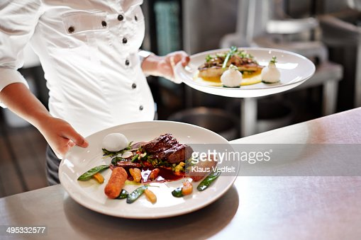 Waiter picking up dishes in kitchen at restaurant