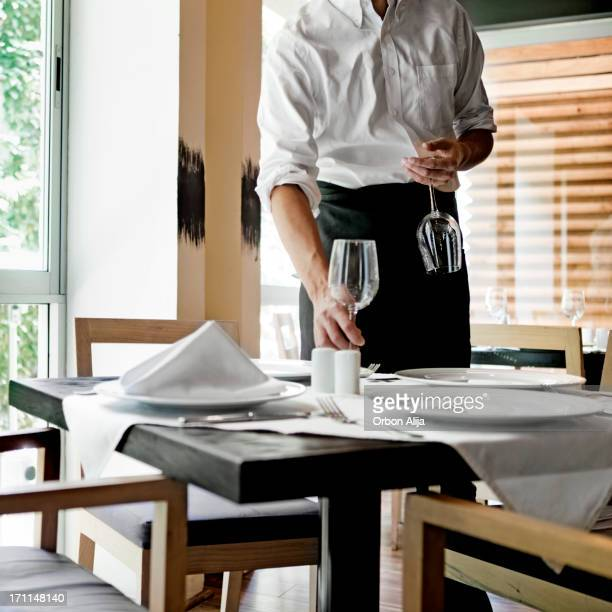 Waiter placing glasses on table in restaurant