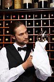Waiter polishing wine glass in restaurant