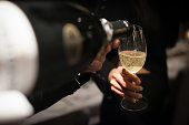 Waiter pouring champagne into the wine glass in restaurant. Blurry background