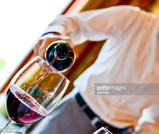 Serveur de verser le vin rouge dans un verre