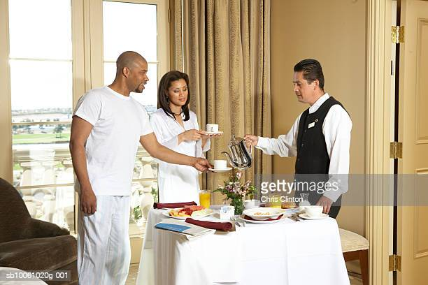 Waiter pouring tea for couple in hotel room