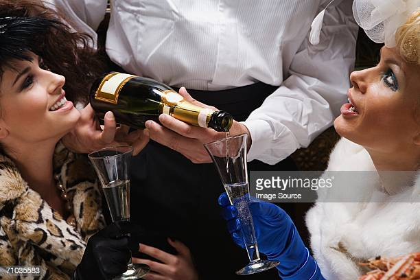 Waiter pouring two women champagne