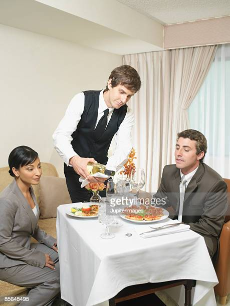 Waiter pouring wine for couple